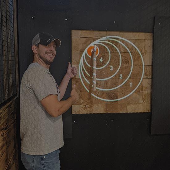 man standing next to bullseye target