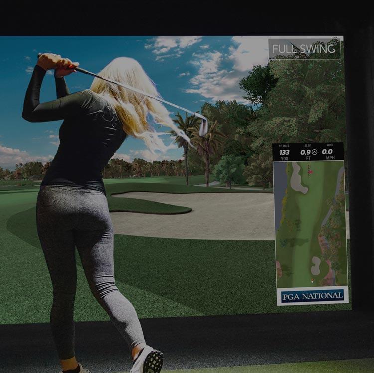 Female playing on golf simulator