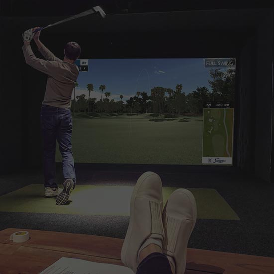 Relaxing and watching friend his a ball on the Indoor Golf Simulator in Ames, IOwa